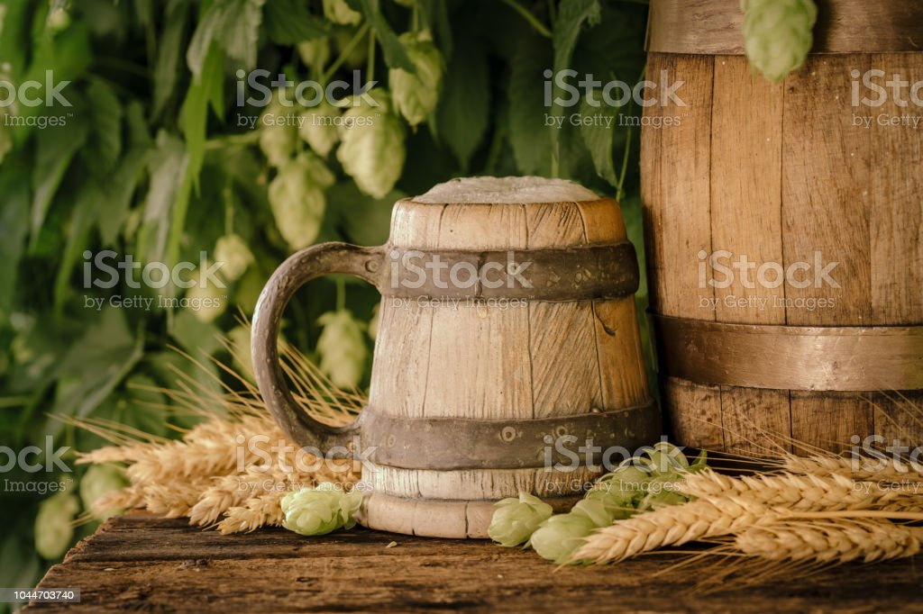 Vintage wooden mug with beer on rustic table. stock photo