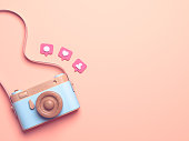 Vintage wooden photo camera with Pin heart, friends, comment, post. Overhead view of Traveler's accessories, Flat lay photography of Travel concept. Pink isolated background. 3d render