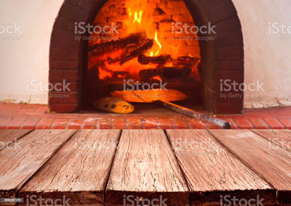 Vintage wooden planks over blurred traditional stove for baking pizza stock photo
