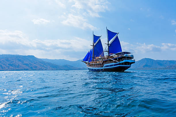 Vintage Wooden Ship with Blue Sails stock photo