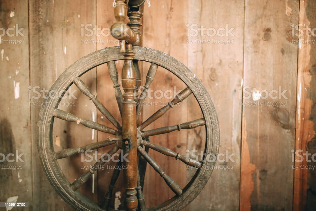 Vintage Wooden Spinning Wheel For Yarn On A Rustic Boardwalk
