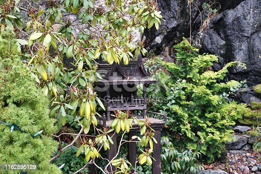Traditional wooden spirit house tucked away among trees and bushes in a quiet outdoor garden