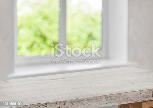 885452818istockphoto Vintage wooden table top with blurred window for product display 1014658192