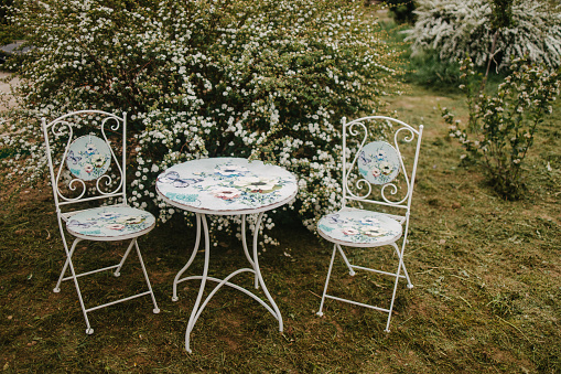Vintage garden furniture with two white wrought iron chairs and a table decorated with floral design decoupage