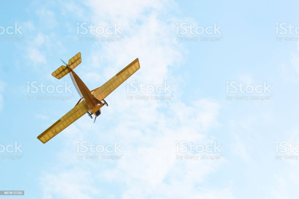 Vintage yellow airplane in blue sky, sky background stock photo