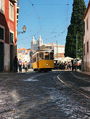 Lisbon, Portugal - October 01, 2018 : Vintage yellow tram on line 28 in Alfama against Church of Sao Vicente of Fora with tourist