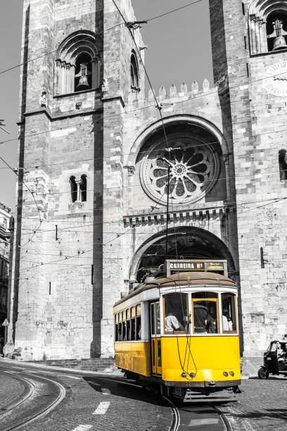 vintage yellow tramway of lisbon in front of the old cathedral. black and white photo with only the tramway in color. - eletrico lisboa imagens e fotografias de stock