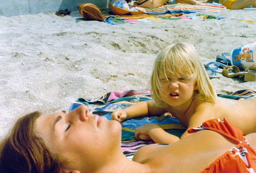 1976 vintage, seventies, retro colourful image of young girl looking up from her beach towel and a sunbathing woman in red bikini.