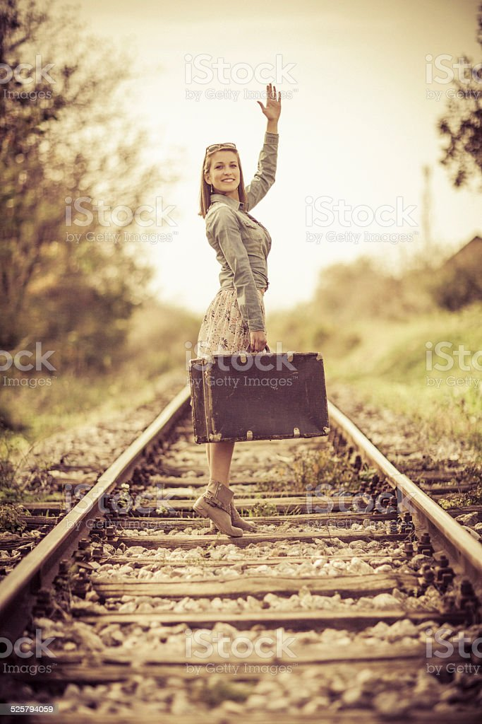 Vintage young woman on railroad tracks stock photo