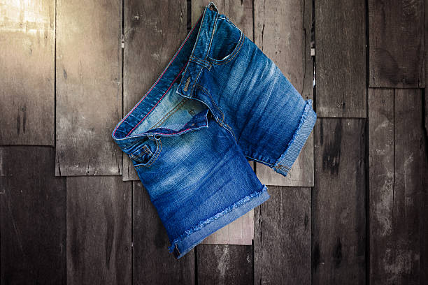 vintage,women's jeans shorts hanging on the wall - jean shorts stock photos and pictures