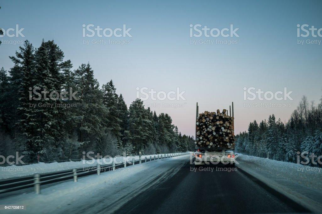 Vinterväg i sverige bakom timmerbil stock photo