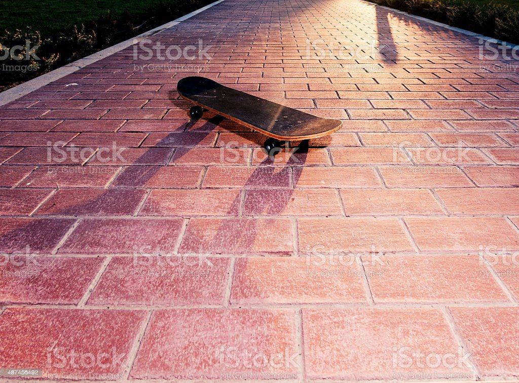 Vintsge skateboard on paved surface backlit. Toned image stock photo