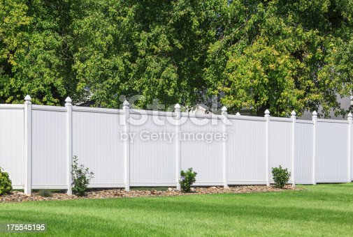 White vinyl fence running across a homeowners back yard.