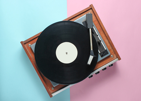 Vinyl player on a blue pink pastel background. Top View