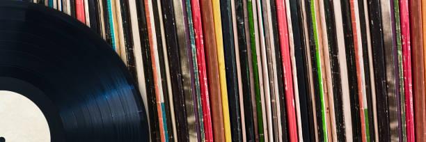 Vinyl-Schallplatte vor einer Sammlung von Alben, Vintage-Musik-Konzept – Foto