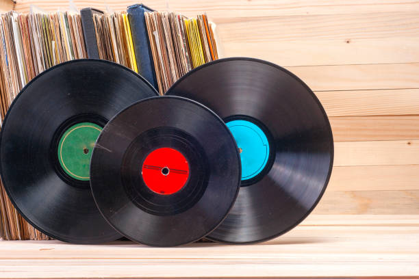 vinyl record in front of a collection of albums, vintage process. copy space for text - records stock photos and pictures