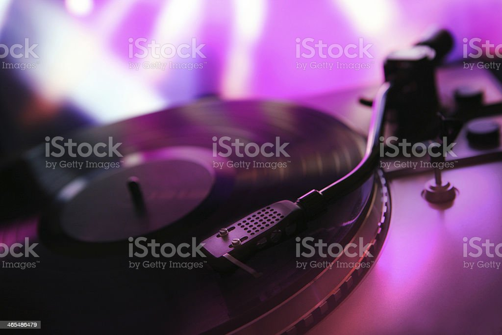 Vinyl record on a turntable in a nightclub colorfully lit stock photo