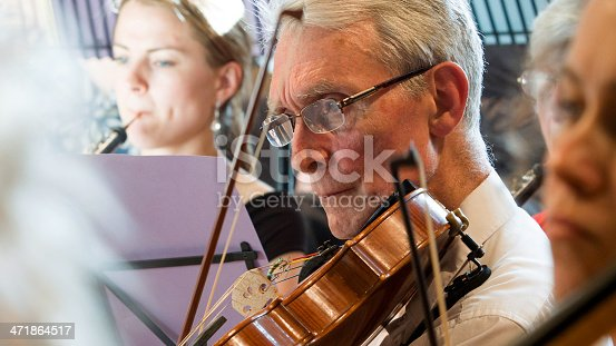 Close detail on the face of a viola player concentrating on his music during an orchestral rehearsal.