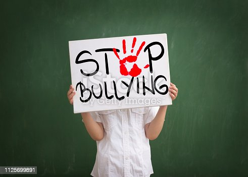 Boy holding a sign with red palm print and text stop bullying