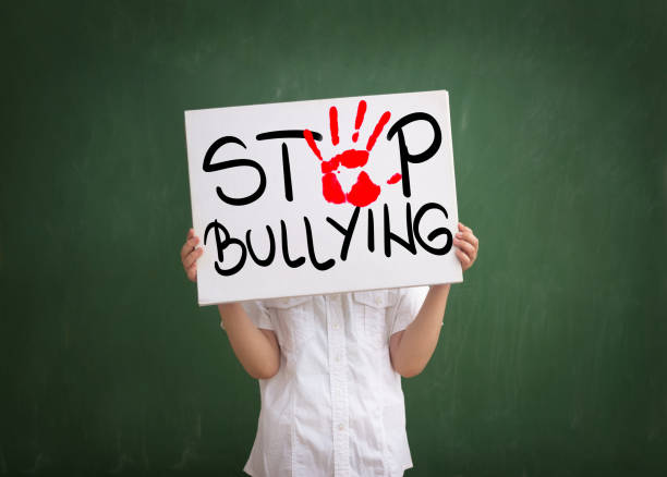Violence in today schools Boy holding a sign with red palm print and text stop bullying former yugoslavia stock pictures, royalty-free photos & images