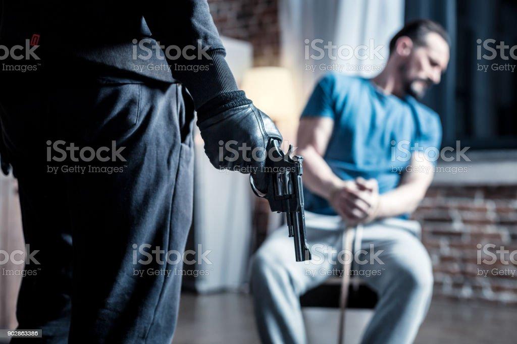 Criminoso violento com uma arma e um homem intimidado - foto de acervo