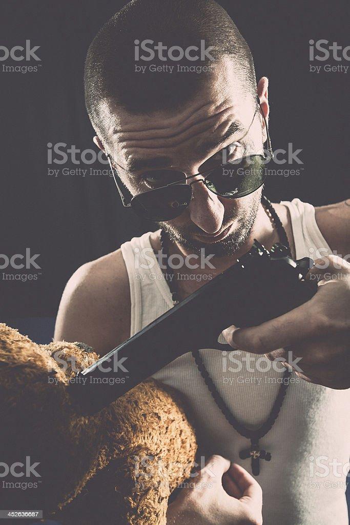 Violent man threating teddy bear with gun royalty-free stock photo