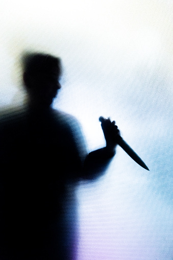 Backlit image of the silhouette of a person, probably a woman, wielding a sharp knife in an aggressive way. The silhouette is distorted, and the arms elongated, giving an alien-like quality. The image is sinister and foreboding, with an element of horror. The image conveys a domestic violence, knife crime theme. Horizontal image with copy space.