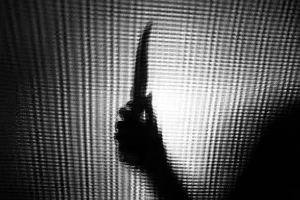 Violenta, ameaçando a silhueta de uma mão segurando uma faca por trás da janela de vidro fosco - foto de acervo