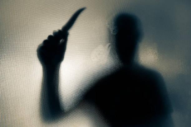 Violenta, ameaçando a silhueta do homem empunhando uma faca por trás da janela de vidro fosco - foto de acervo