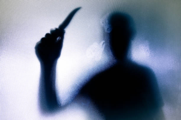 violent threatening silhouette of man wielding a knife behind frosted glass window - killer stock photos and pictures