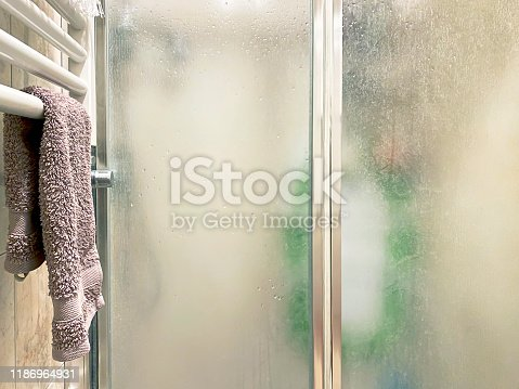violet colored towel laid out on a white radiator near the shower enclosure with frosted glass doors and aluminum structure inside a bathroom. Interior shot