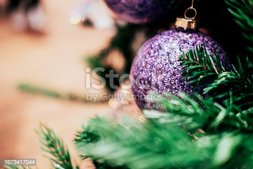 istock Violet holographic sequin ball among Christmas decorations. 1073417044