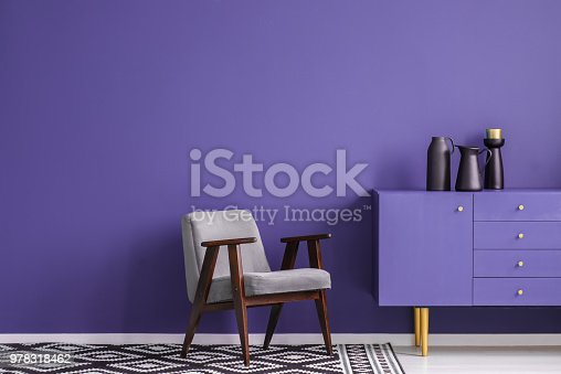 Grey armchair on patterned carpet next to violet cabinet with black vase in living room interior with copy space