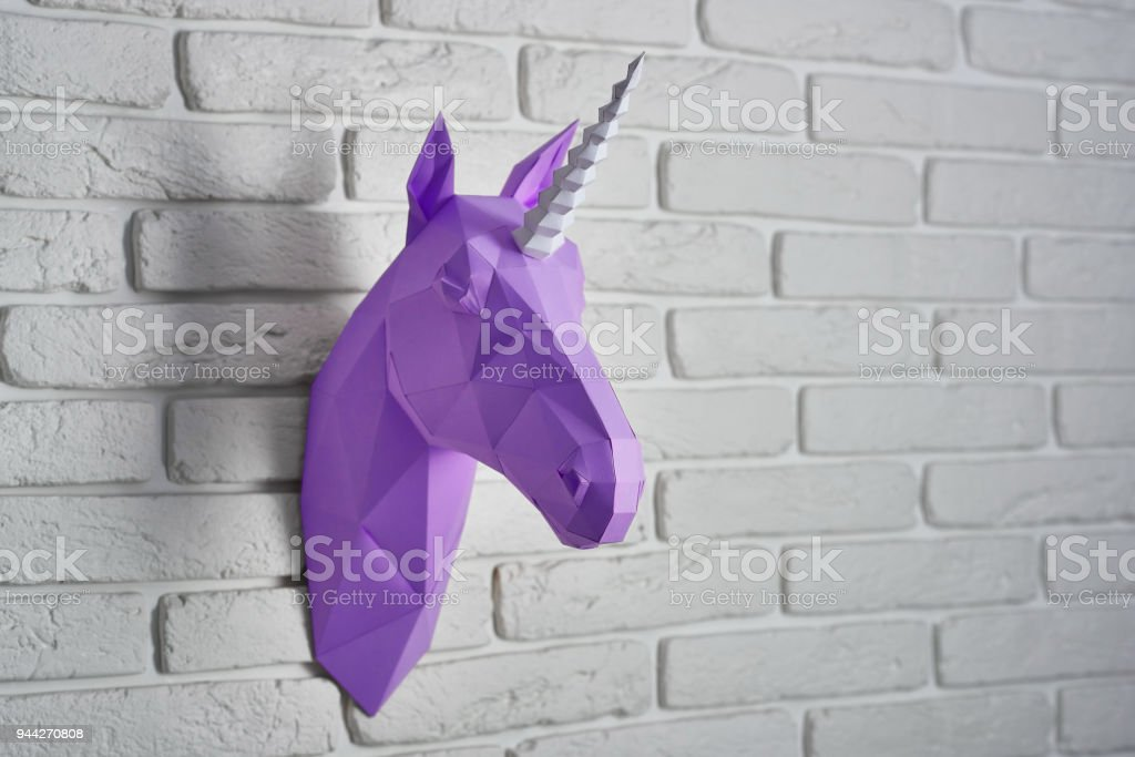 violet paper unicorn's head hanging on the wall. stock photo