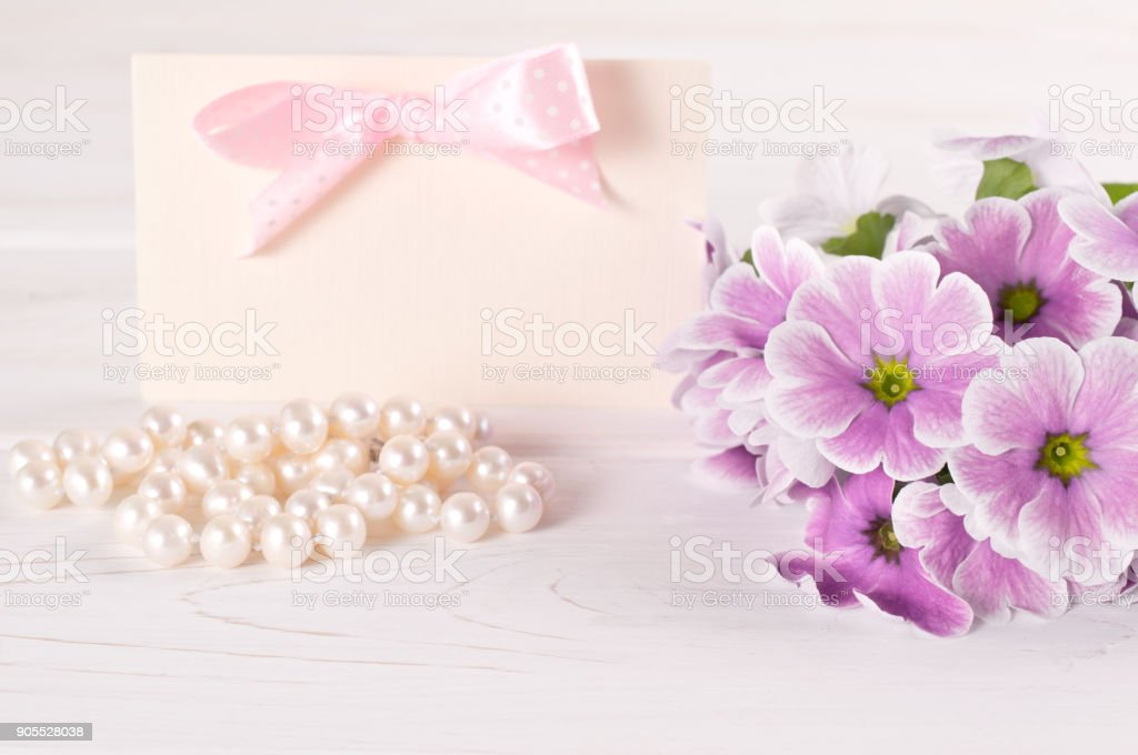 Violet primroses with greeting card and pearl necklace stock photo