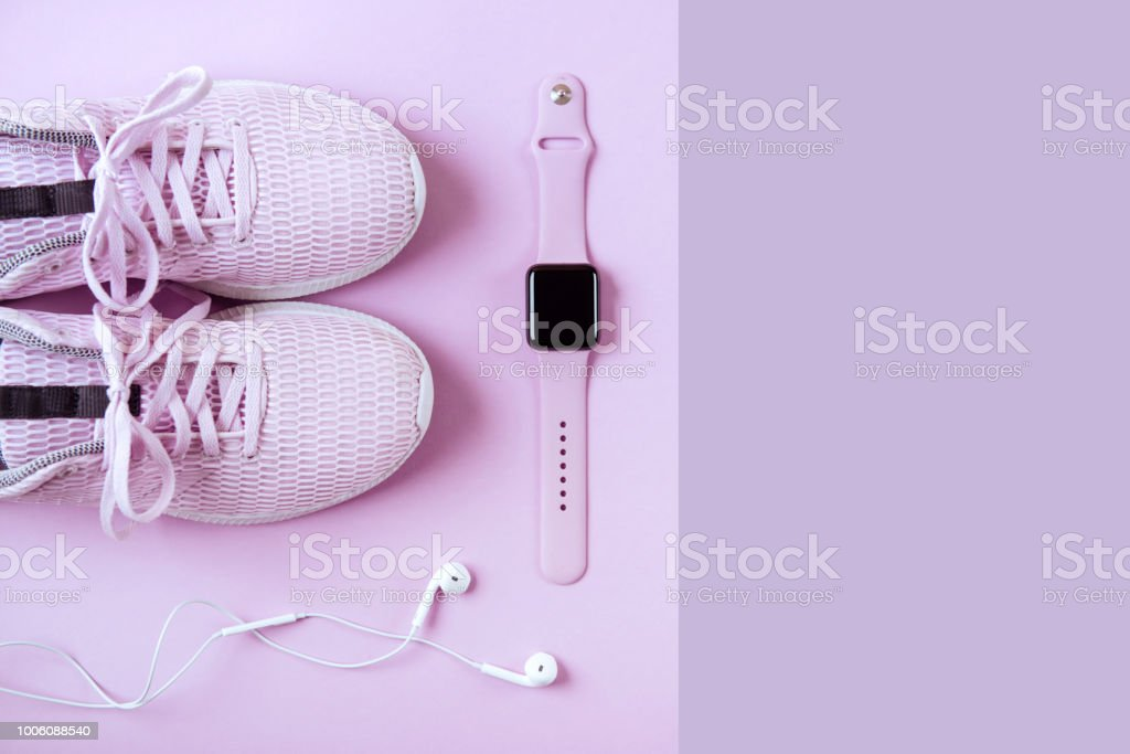 Violet sneakers, headphones and watcheson pink background. stock photo