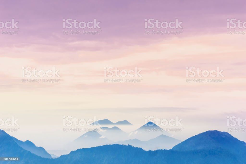 Violet sunset over foggy volcanoes of Lago Atilan by Quetzaltenango in Guatemala stock photo