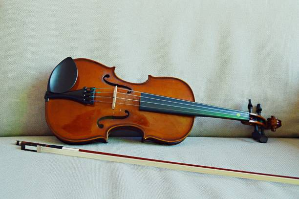 A violin and bow placed horizontally  on a white self chequered background couch, a horizontal shot stock photo