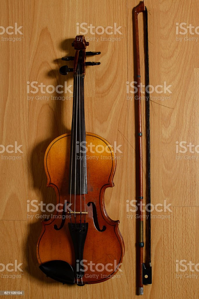 violin and broken bow lying on the wooden floor stock photo