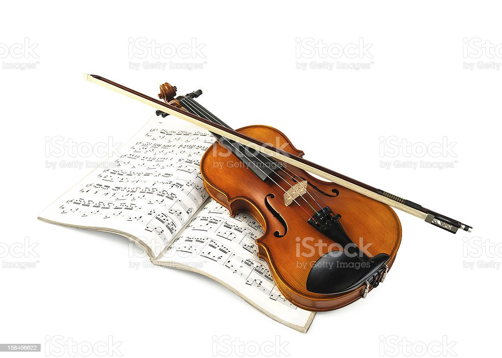 Violin and fiddle stick over score isolated on white stock photo
