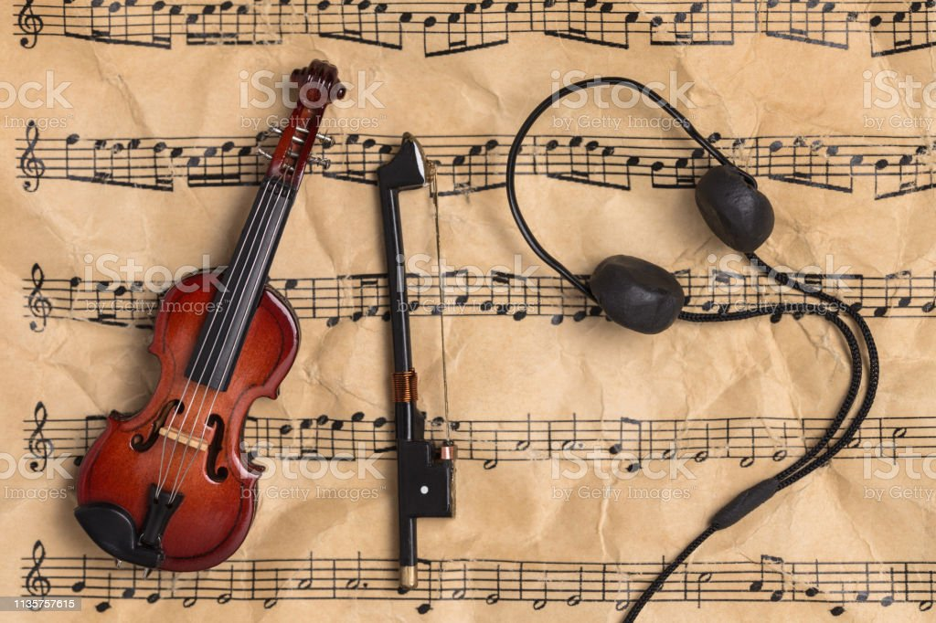 Violin and headphones on old paper music notes with copy space