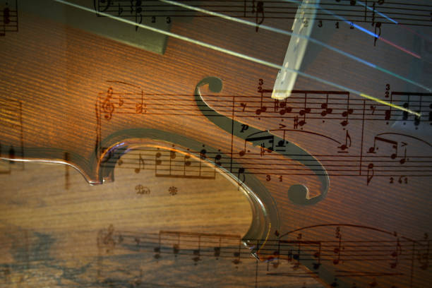 Violin and note Violin waist detail and note. Multiexposition. Shallow depth of field string instrument stock pictures, royalty-free photos & images