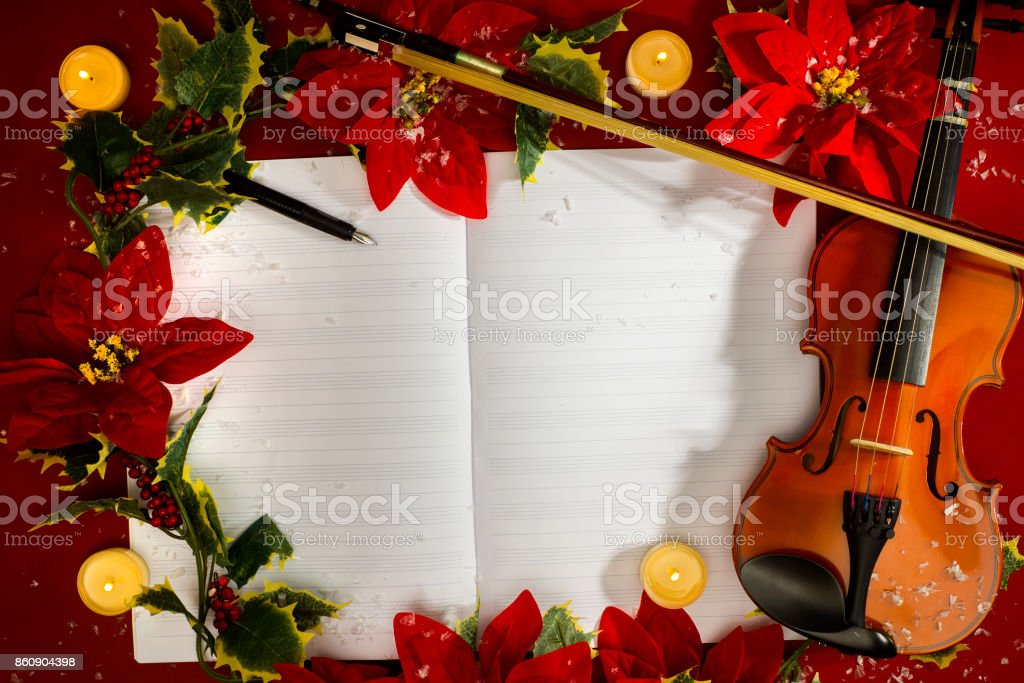 Violin and open music manuscript on the red background. Christmas concept stock photo