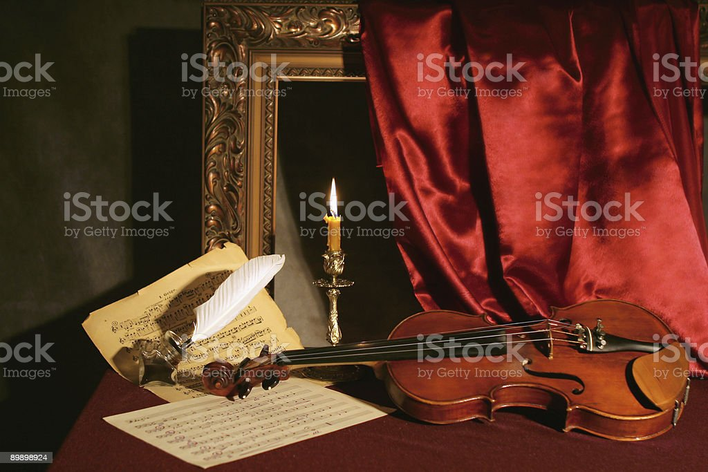 violin, candle  and feather with ink on music sheets stock photo