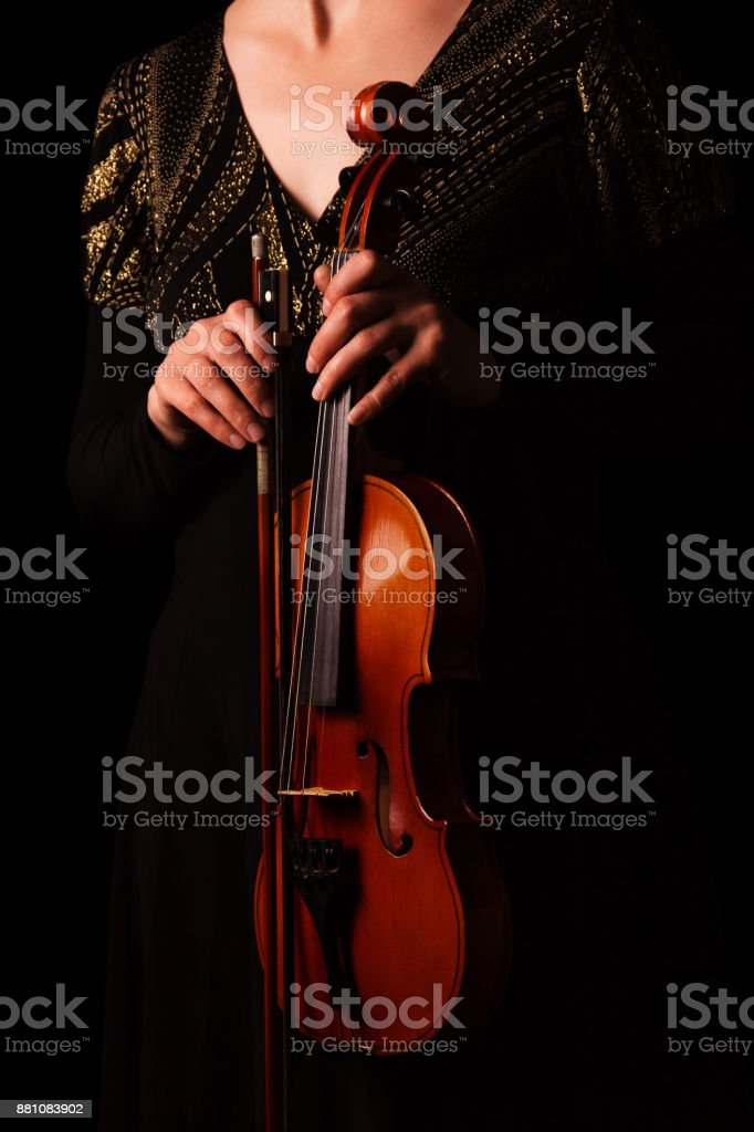 Violin in the hands of women before the concert, isolated on black stock photo