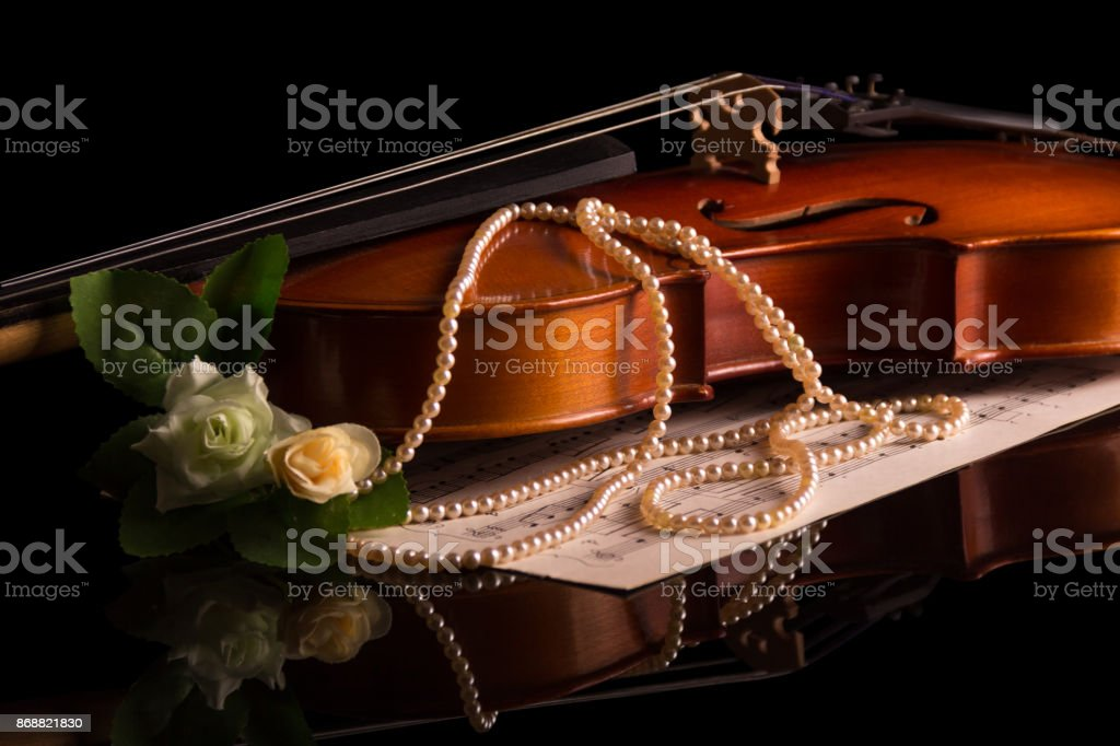 Violin lies on the table, next to musical notes isolated on black stock photo