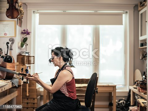 Hispanic Female Violin Maker in her shop fixing the fine veneer finish of the cello. Portrait of the modern woman for Nosotros Collection.