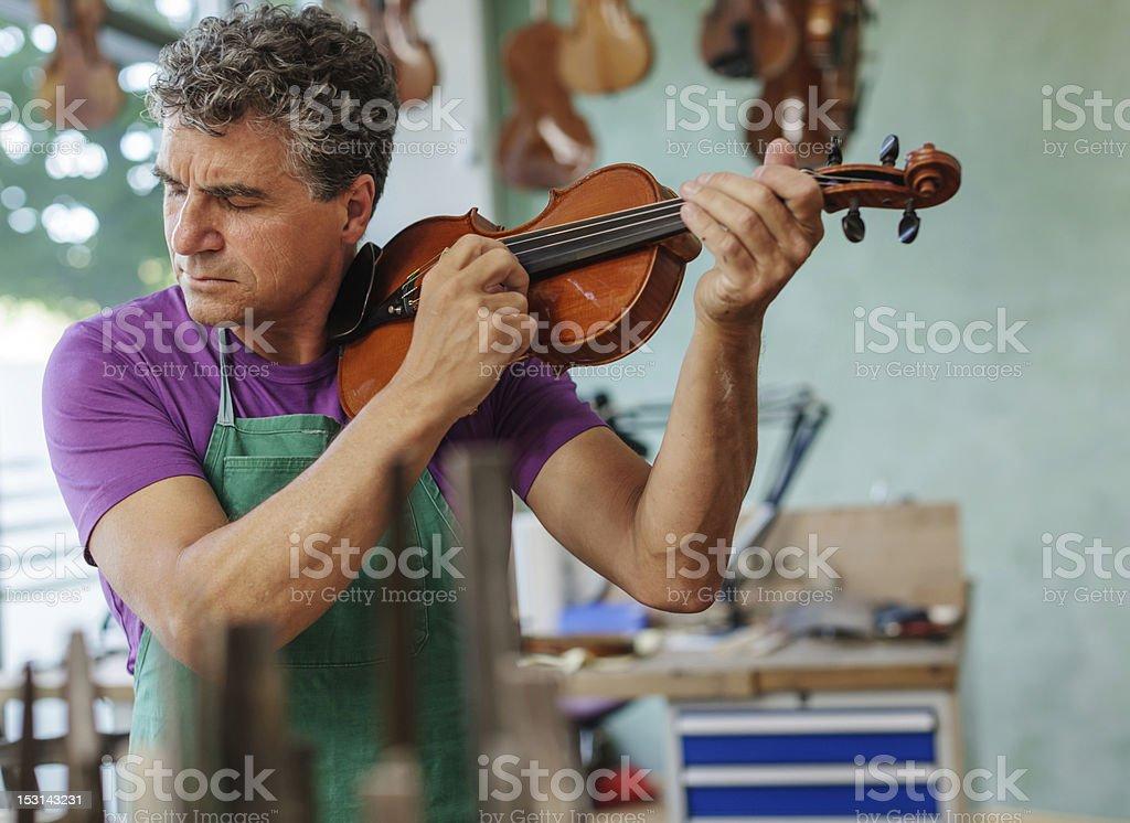 Violin Maker Testing an Instrument stock photo