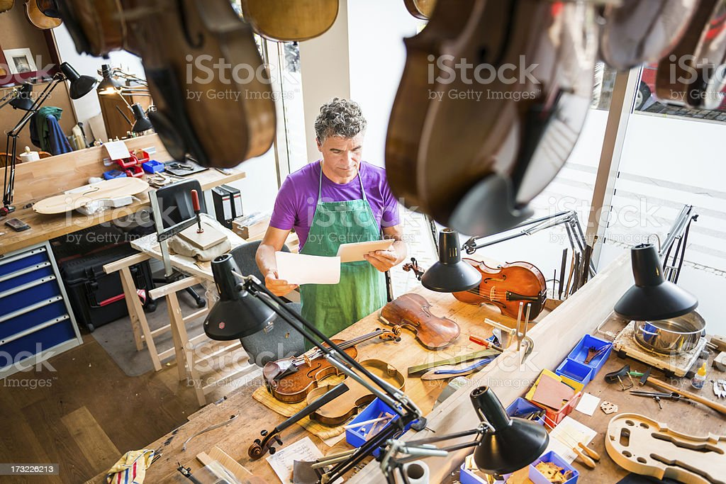 Violin Maker with Tablet PC royalty-free stock photo