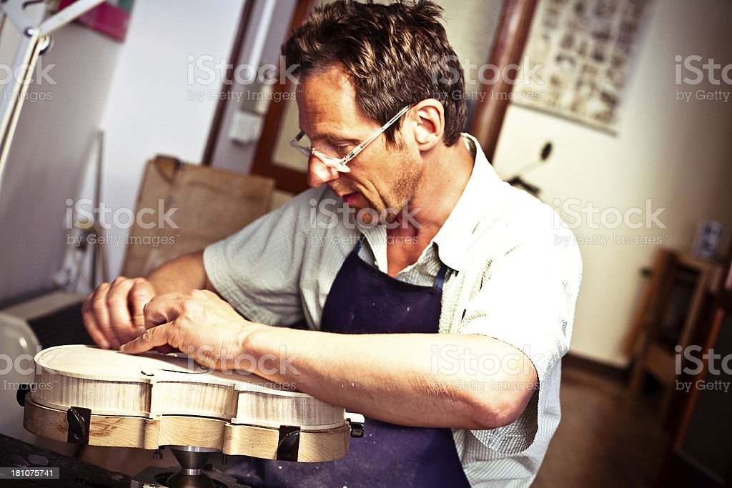 """Violin Maker Working in Cremona, Italy """"Violin maker in Cremona. From the 16th century onwards, Cremona was renowned as a centre of musical instrument manufacture."""" 40-49 Years Stock Photo"""